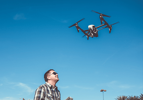 A man is controlling a flying drone